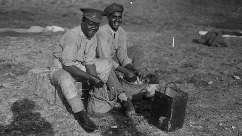 Deux soldats noirs sont assis sur une petite boite et lave des vêtements dans une petite poche en tissu remplie d'eau. Ils sourient.