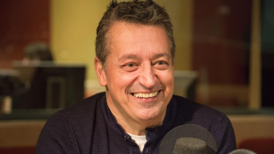 Il sourit devant un micro.