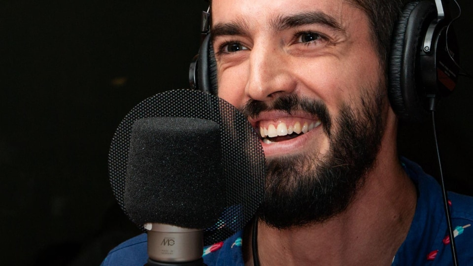 L'homme barbu sourit à belles dents.
