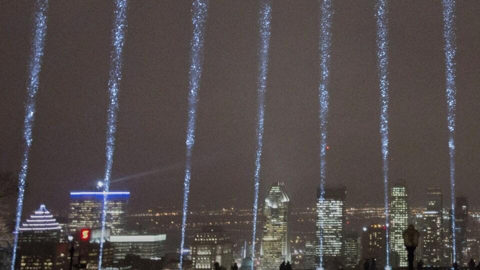 Faisceaux bleutés s'élevant au-dessus de la ville de Montréal.