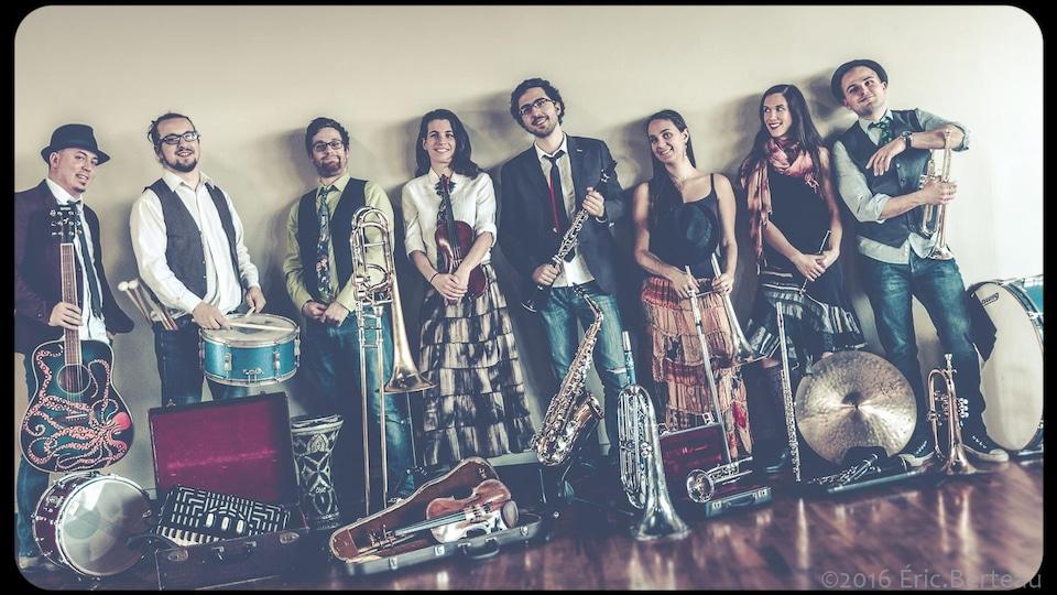Huit personnes sont alignées contre un mur et sourient en tenant un instrument.