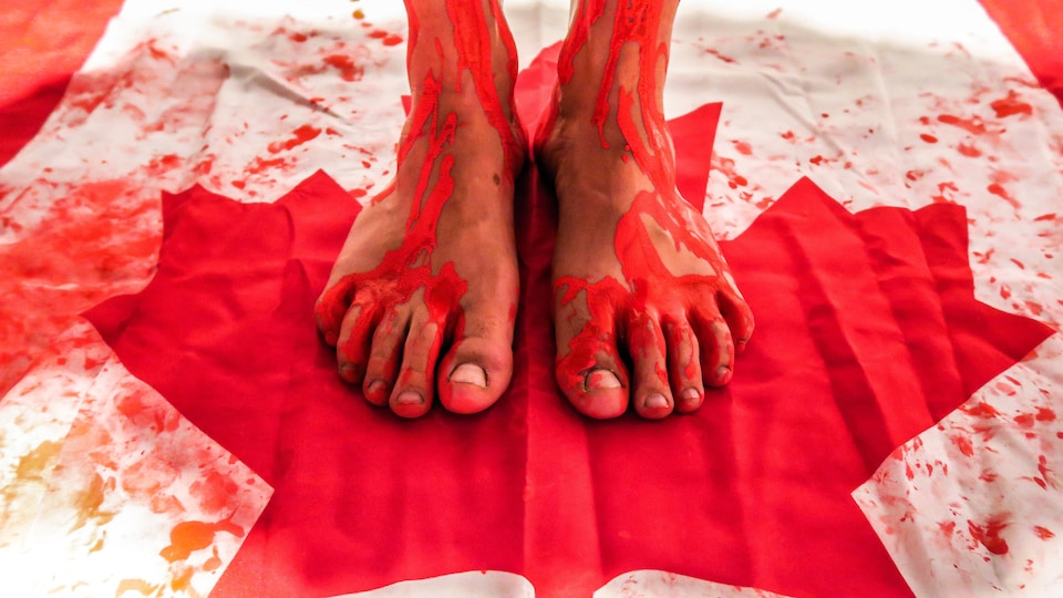 Un drapeau canadien piétiné, maculé de peinture rouge, qui représente le sang.