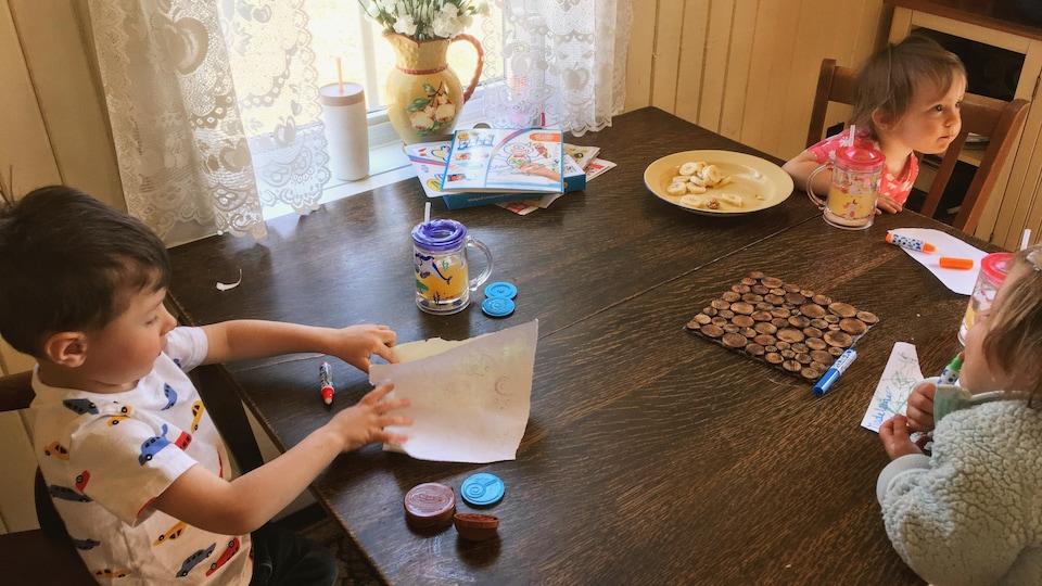 Trois enfants font du bricolage assis à une table.
