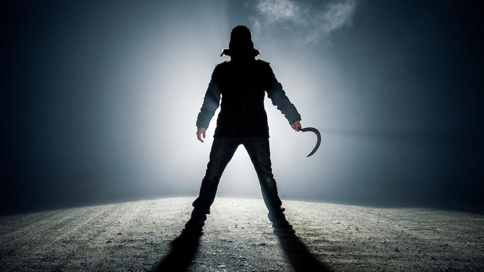 Un homme avec une hache dans l'ombre.