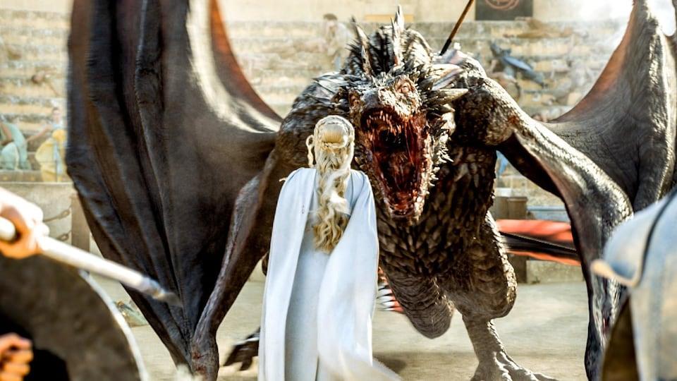 On voit Daenerys Targaryen (Emilia Clarke) de dos, avec un immense dragon, la bouche ouverte, qui s'approche d'elle. La scène est tirée de la série « Game of Thrones ».