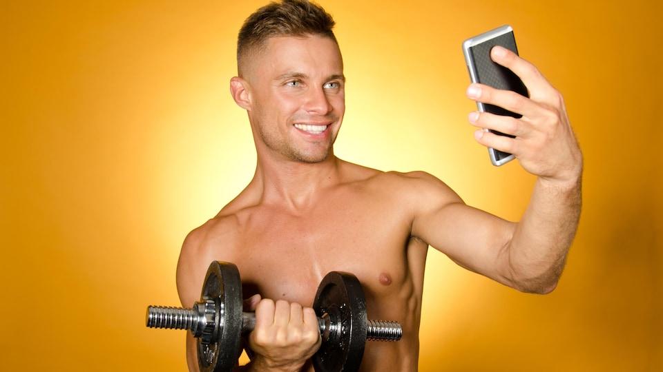 Un homme torse nu tenant un haltère se prend en photo.