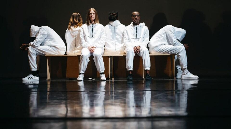 Les six interprètes habillés de combinaisons blanches sont assis sur un banc.