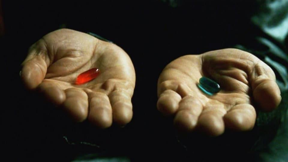 Deux mains tendues, celle de gauche avec une pilule rouge et celle de droite avec une pilule bleue.