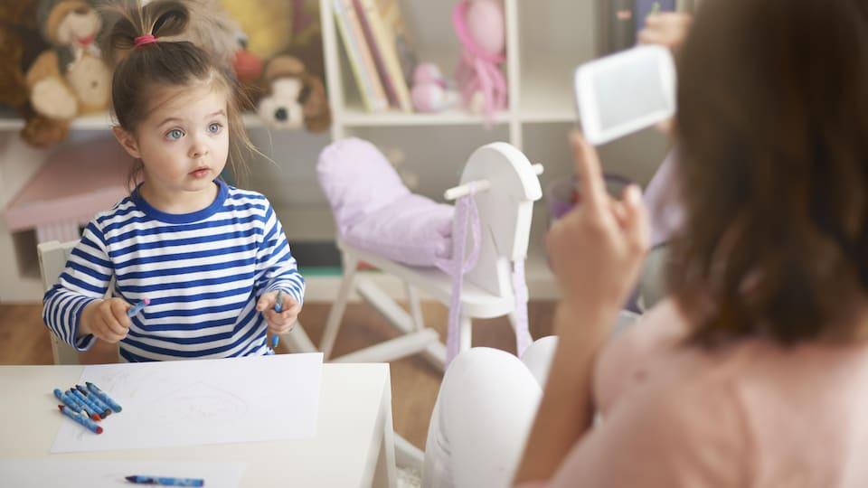 Une femme prend une photo d'une enfant avec un téléphone.