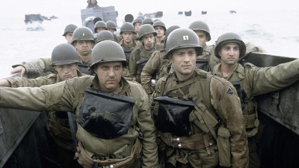 Des soldats en uniforme dans un bateau, le regard porté au loin.