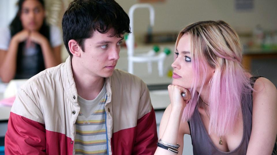 Un garçon et une fille adolescents se regardent dans les yeux, assis à une table.
