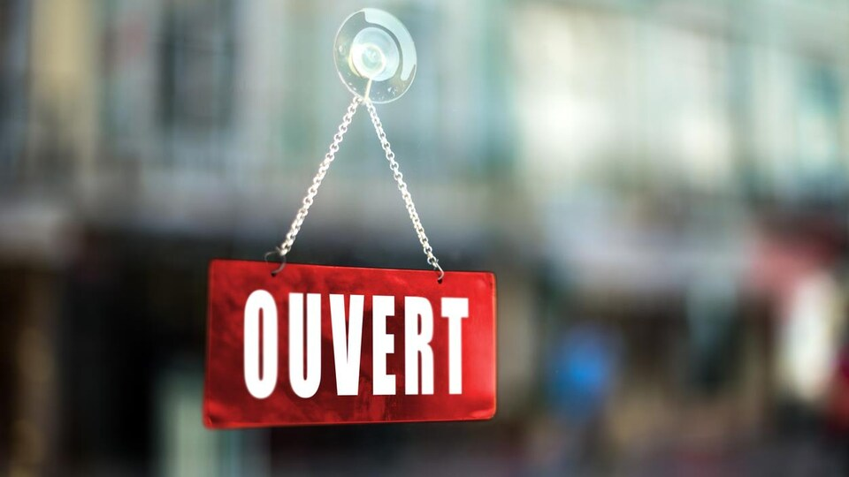 Gros plan sur une pancarte Ouvert d'une fenêtre d'un commerce.