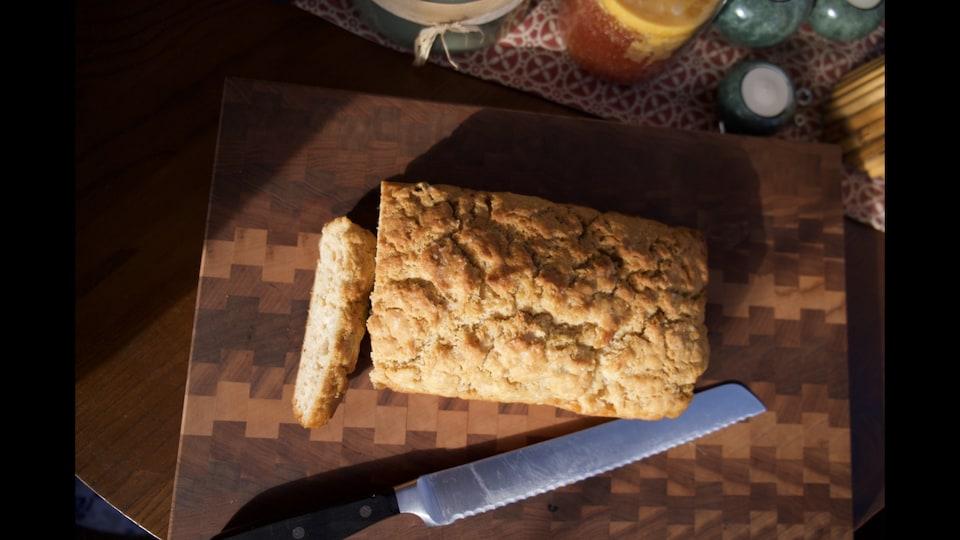 Un pain sur une planche de bois à côté d'un couteau à pain.