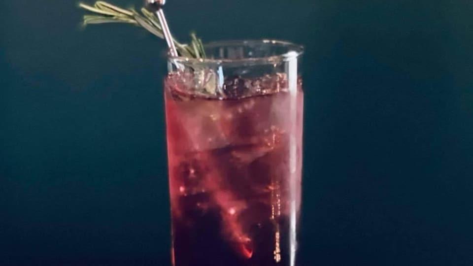 Un verre rempli de boisson rouge avec des feuilles de romarin.