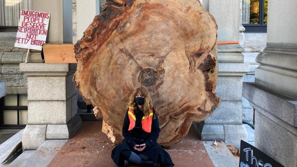 Une manifestante assise devant un immense tronc d'arbre.