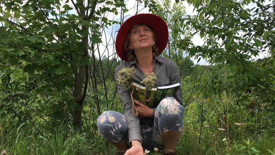 Une femme portant un chapeau accroupie dans un paysage de végétation et tenant des livres et des bouquets de fleurs.