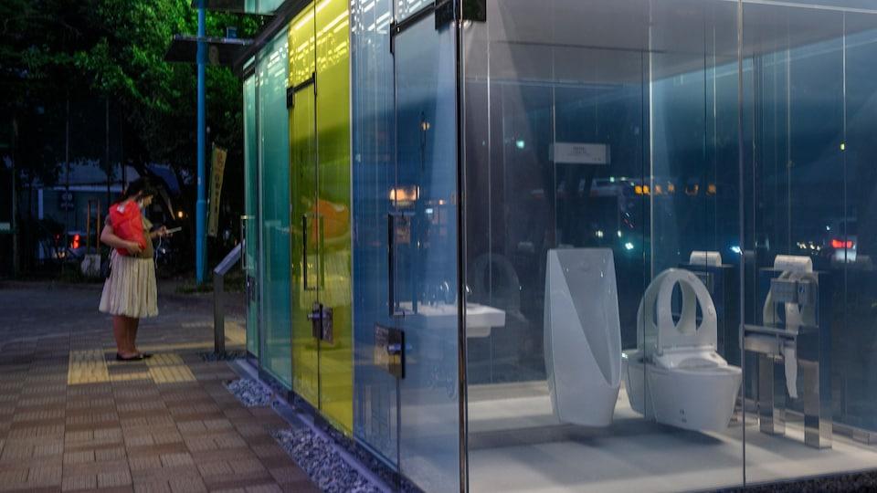 Une femme se tient devant des toilettes publiques, dont les murs sont transparents et colorés.