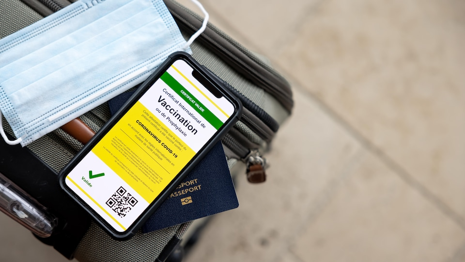 Un passeport vaccinal sur une valise.