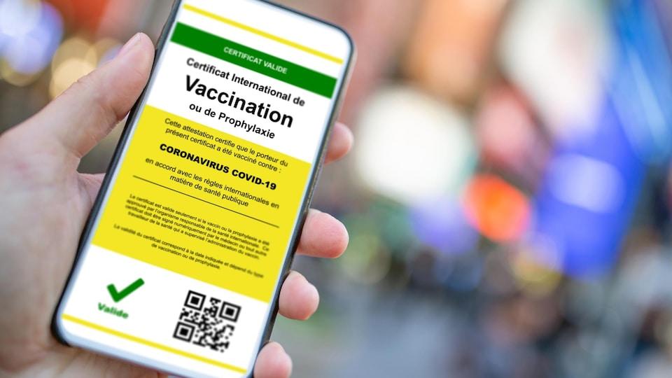 Gros plan sur une main tenant un téléphone avec une application attestant que le porteur a été vacciné contre la COVID-19.