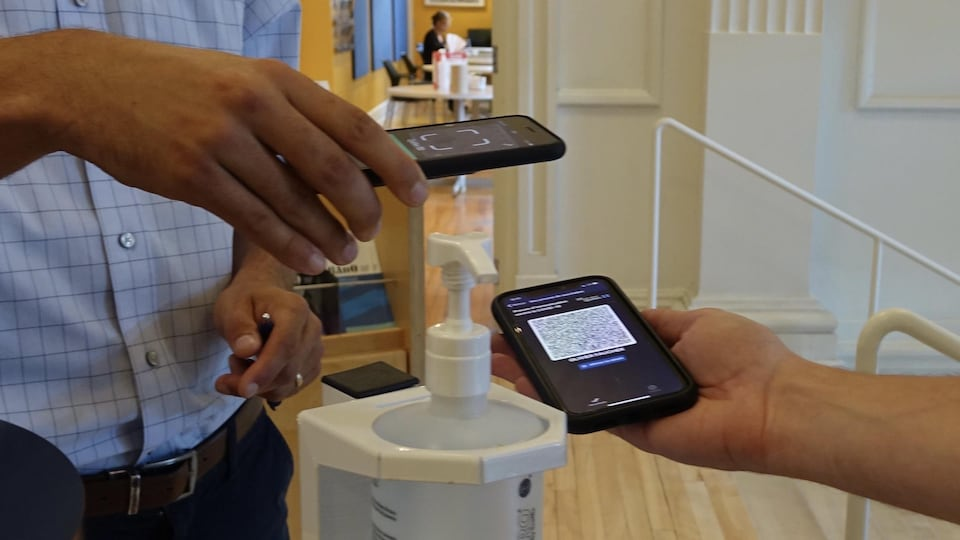 Une personne présente son code QR sur son téléphone portable à un homme muni d'une application pour en valider l'authenticité.