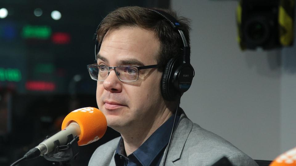 Un homme en costume gris clair aux yeux bleus et portant des lunettes de vue est devant le micro.