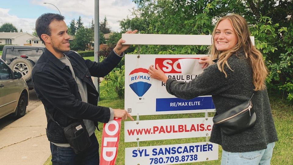 Stéphanie Blais et Paul Cournoyer à côté de l'affiche de vente de la maison.