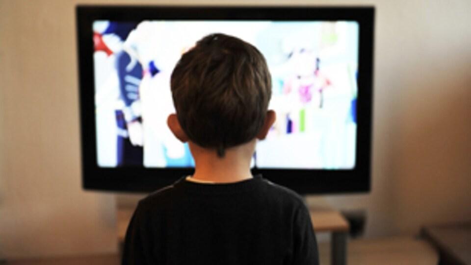 Un enfant de dos regarde la télévision.
