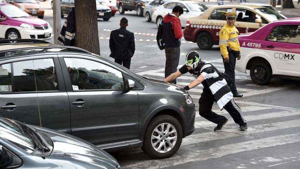 Un homme vêtu d'un habit de lutteur mexicain, les deux mains posées sur le capot d'une voiture en plein milieu d'un passage piétonnier.