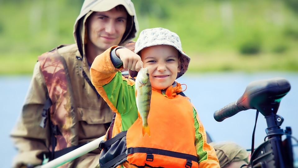 Un garçon souriant dans une chaloupe tient un poisson qu'il vient de pêcher.