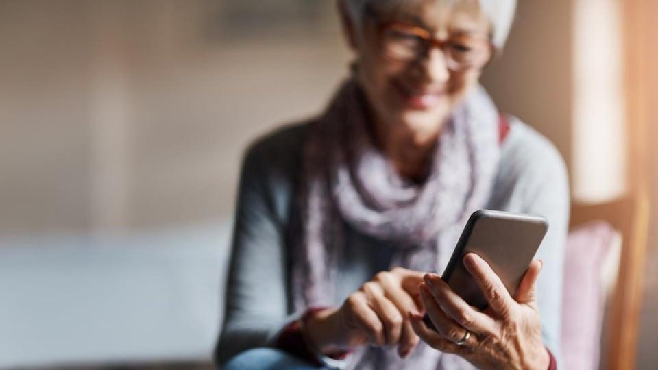 Une femme dans la jeune soixantaine regarde son cellulaire.