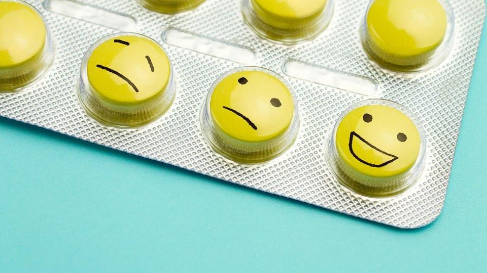 Des faces de bonhommes tristes, confus et heureux sont dessinées sur des pilules.