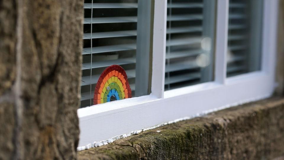 Un arc-en-ciel est affiché sur la vitre de la fenêtre d'une maison.