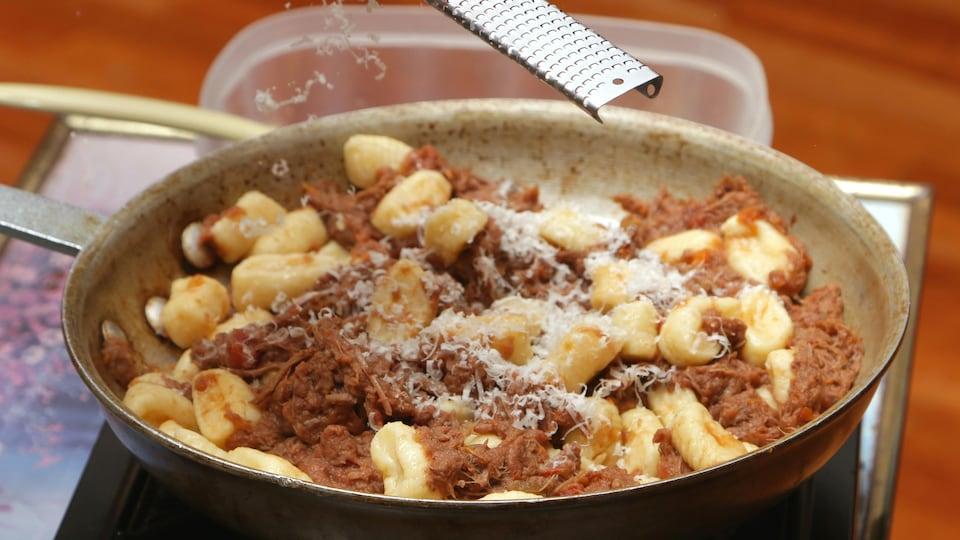 Bob le Chef râpe du parmesan au-dessus d'une poêle remplie de gnocchis dans une sauce à la viande.