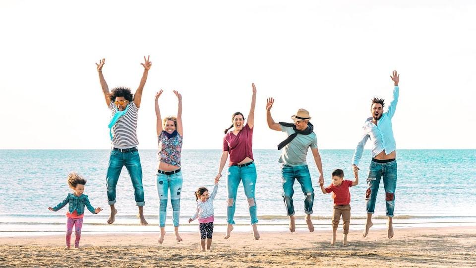 Un groupe de cinq adultes et trois enfants sautent sur une plage.