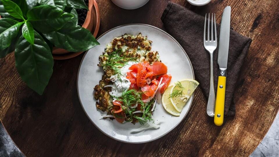 Une assiette garnie de crêpes de légumes, saumon fumé et yaourt grec.
