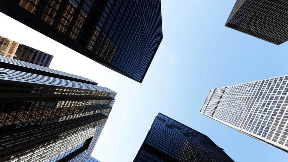 Vue en contre-plongée de cinq hauts immeubles qui se découpent sur un ciel bleu immaculé.