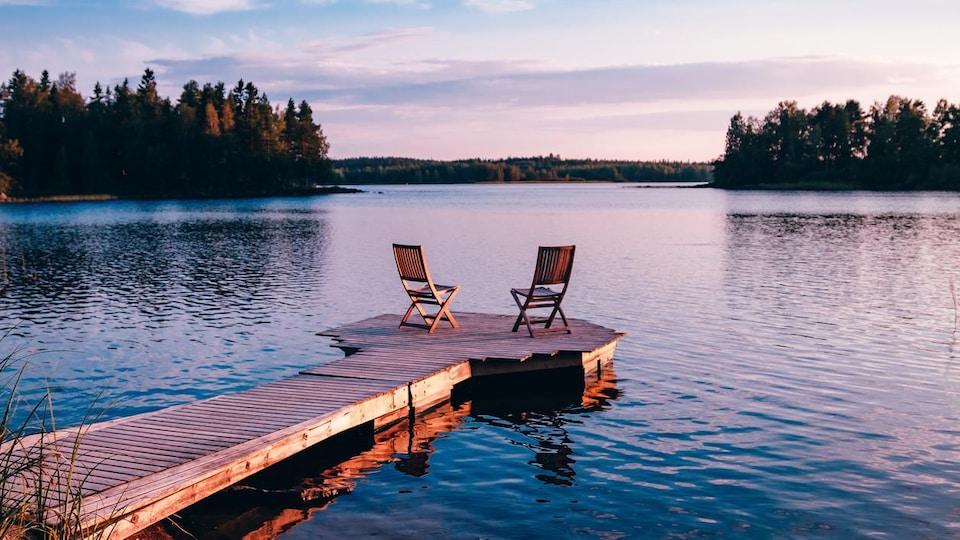 Deux chaises vides sur une plateforme flottante sur un lac au coucher du soleil.