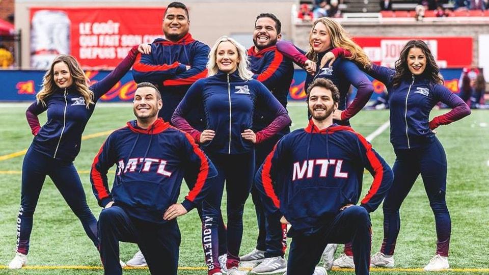 Des hommes et des femmes posent sur un terrain de football en tenue de cheerleaders des Alouettes de Montréal.