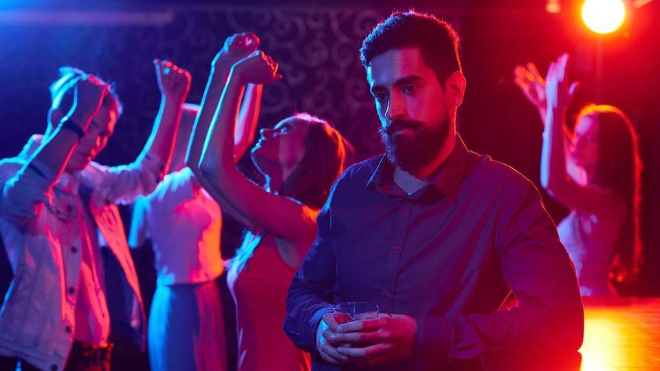 Un homme est appuyé contre un bar seul alors que des gens dansent en arrière de lui.