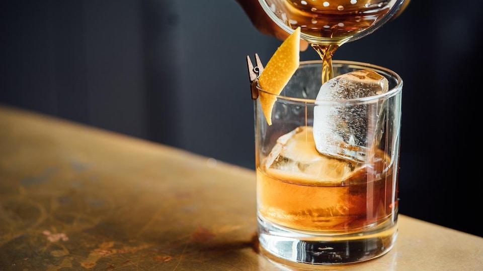Photo d'un cocktail versé dans un verre avec de la glace et une pelure d'orange.