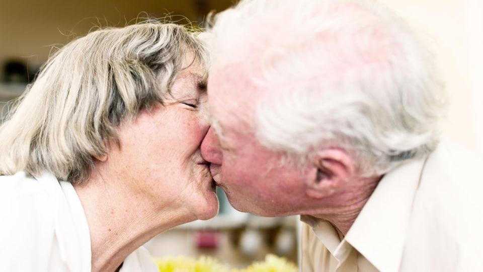 Une femme et un homme âgés se font un baiser sur la bouche.
