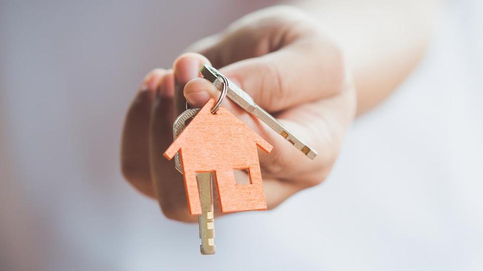 Une main tient des clés avec un porte-clés en forme de maison.