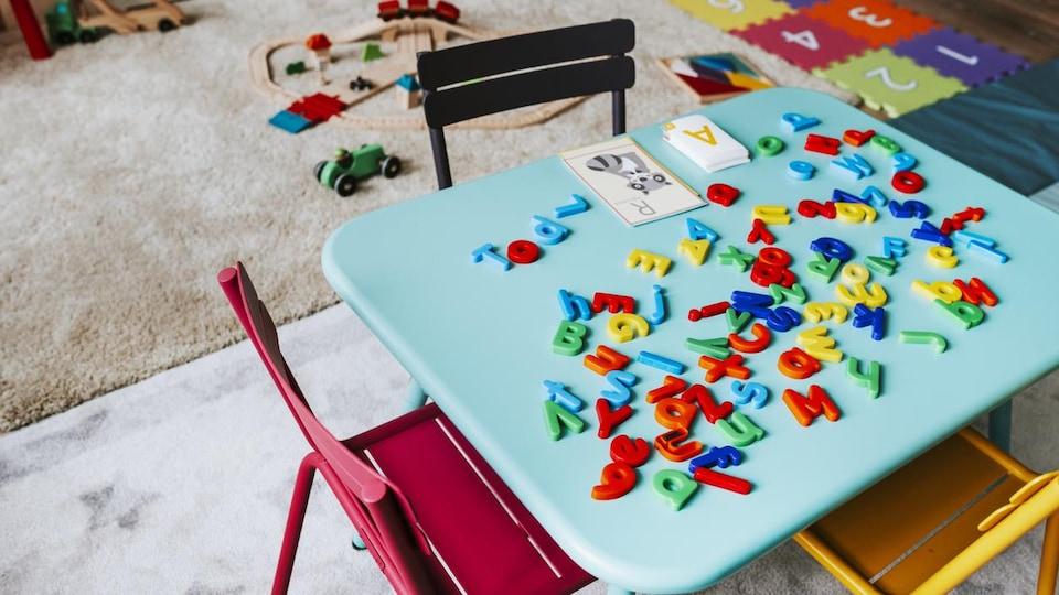 Une petite table pour enfants est recouverte d'un jeu avec des chiffres et des lettres dans une salle qui accueille des enfants.