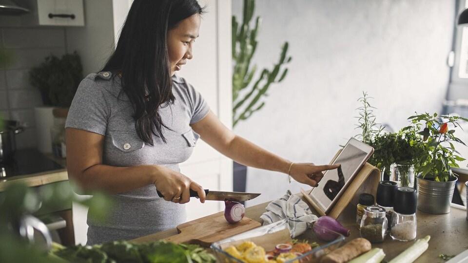 Une femme coupe des légumes en regardant une recette sur une tablette.