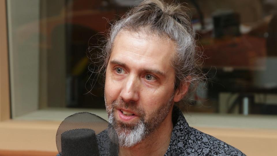 Photo de Dany Bouchard devant un micro de radio.