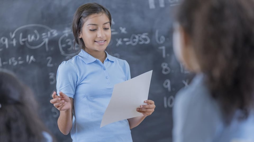 Une fille parle devant un tableau noir en lisant une feuille devant les autres élèves.