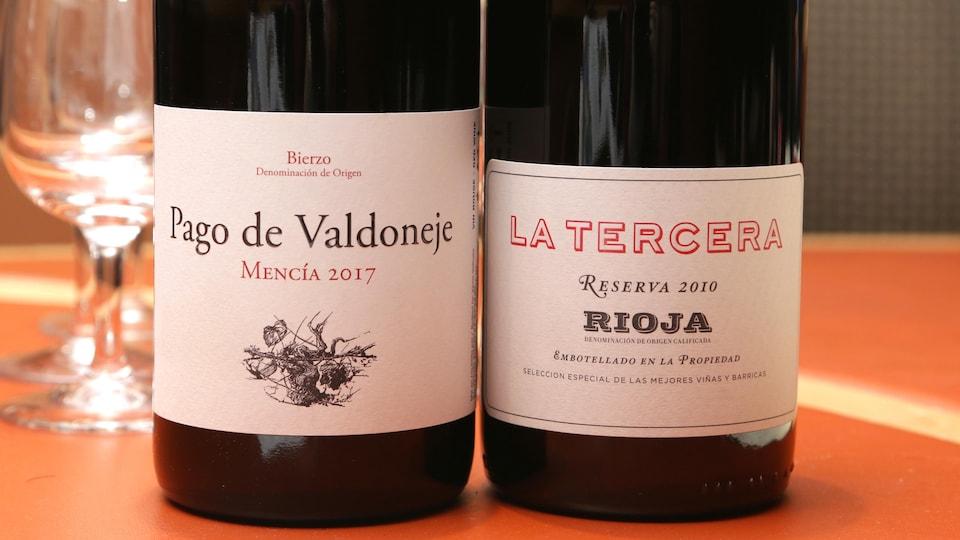 Gros plan des étiquettes de deux bouteilles de vin rouge.
