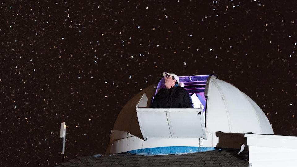 Tim Doucette regarde le ciel étoilé à partir du dôme de son observatoire.