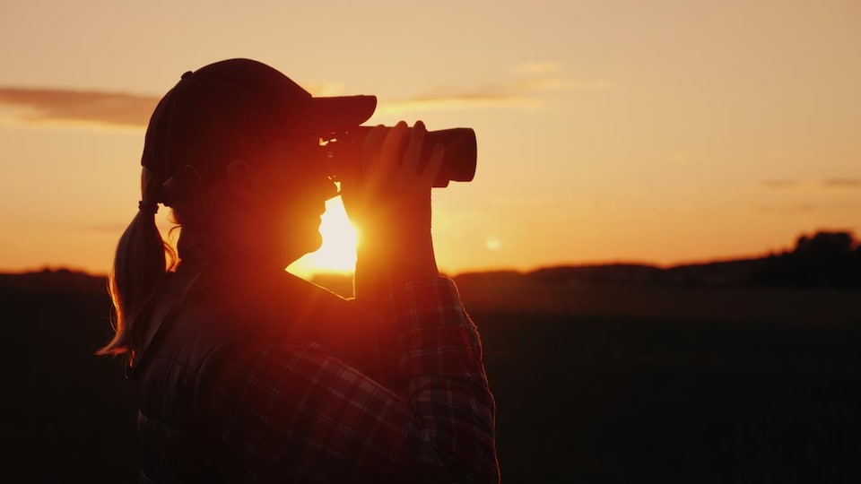 Photo de profil devant un coucher de soleil.