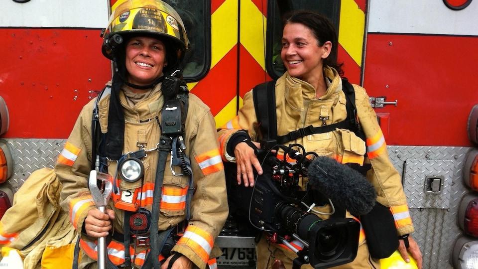 Deux femmes en tenue de pompière, l'une tient une caméra à la main.